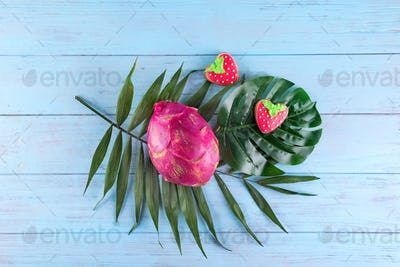 Tropical dragon fruit with homemade glazed cookies served on palm leaves on blue wooden background