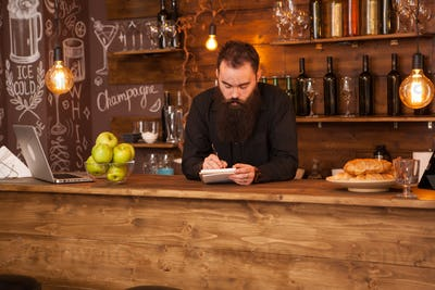 Bearded hipster bartender taking notes in vintage pub