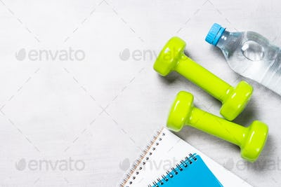 Dumbbells, notepad, water and apple top view.