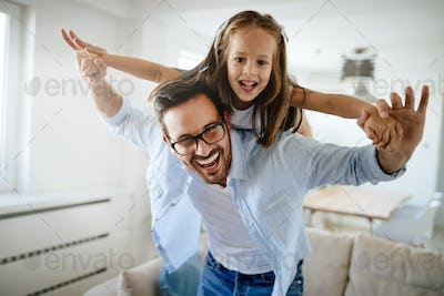 Portrait of father and daughter playing at home