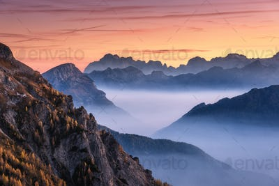 Mountains in fog at beautiful sunset in autumn. Dolomites, Italy