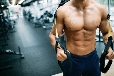 Young handsome man doing exercises in gym