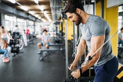 Muscular bodybuilder guy doing exercises in gym