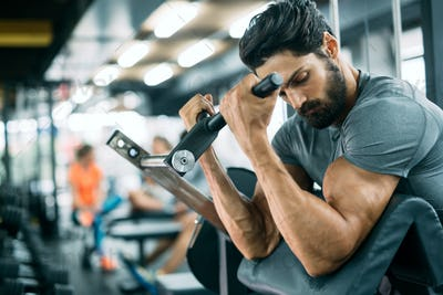 Strong ripped man training in modern gym