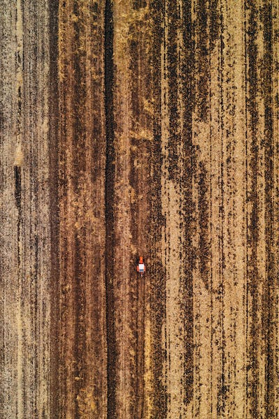 Aerial view of agricultural tractor plowing field