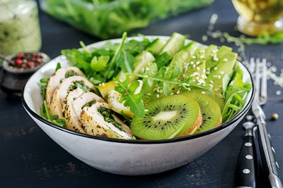 Buddha bowl dish with chicken fillet, avocado, cucumber, fresh arugula salad and sesame.