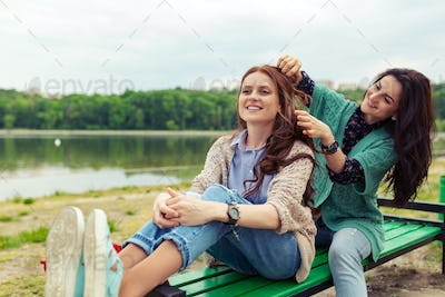 Two beautiful girls relaxing while making hairdo enjoying time together