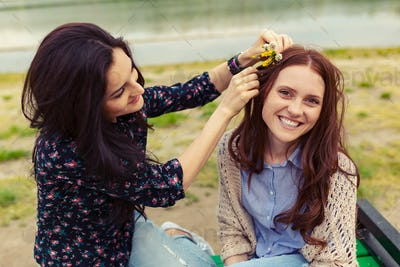 Two pretty sisters girls having fun together, field flowers in hair