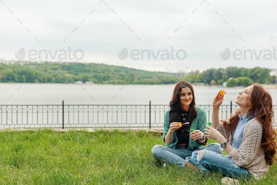 Two sisters having fun while making bubbles and sitting on the grass