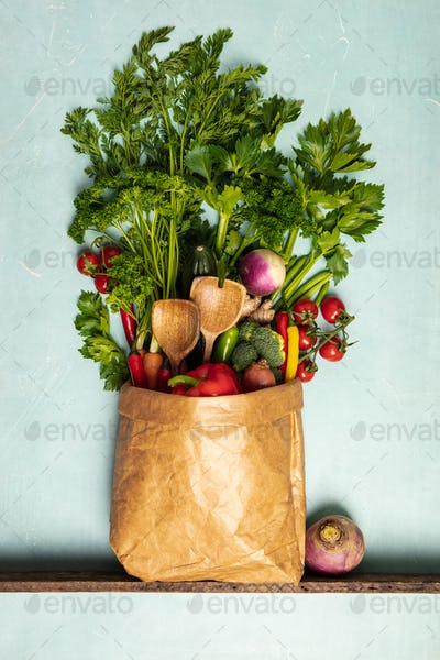 Grocery shopping concept. Different food in paper bag on colorfu