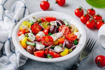Greek salad with fresh cucumber, tomato, lettuce, capers, red onion, feta cheese and olives.