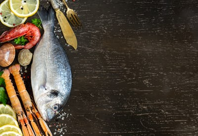 Fresh dorado fish, seafood and vegetables on a dark background