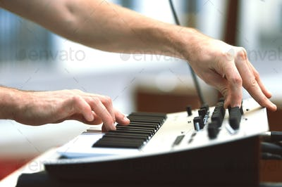 A synthesizer player during a concert moves knobs and controls t