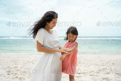 daughter look his arm when a mother rub sunblock