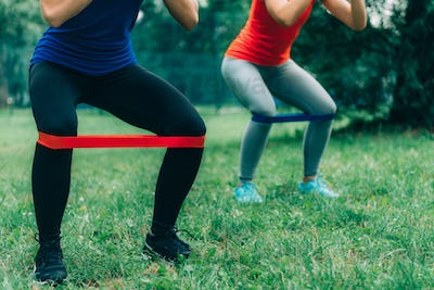 Women Exercising with Elastic Bands in a Park