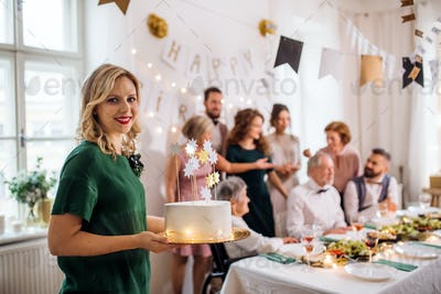 A young woman holding a birthday cake on an indoor party.