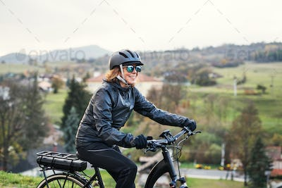 A side view of senior woman with electrobike cycling outdoors in countryside.