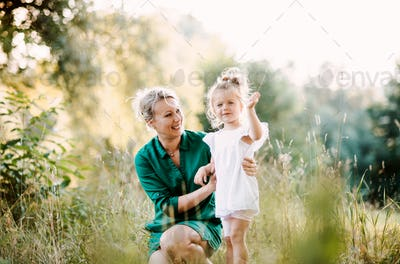 Young mother in nature holding small daughter in summer.
