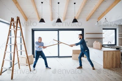 Two men having fun when furnishing new house, a new home concept.