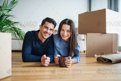 A young couple with a cup and cardboard boxes moving in a new home.