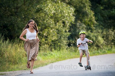 A small boy riding scooter and mother running on a road in park on a summer day.