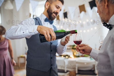 A man pouring guests wine on a indoor family birthday party.