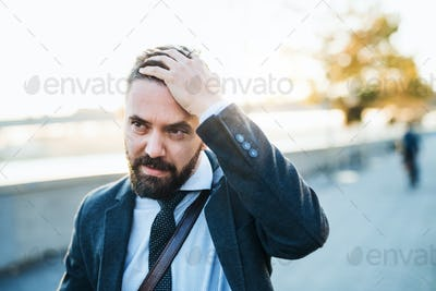 Worried businessman walking in city at sunset. Copy space.