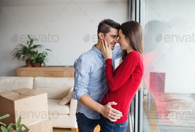 Young couple moving in a new home, hugging.