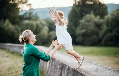 Young mother in nature with small daughter, having fun.