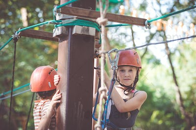 little brother and sister make climbing in the adventure park.