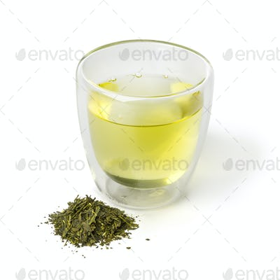 Cup of Japanese green tea and a heap of dried green tea leaves