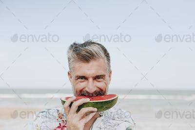 Mature man eating watermelon at the beach