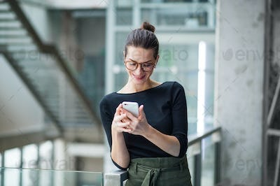 A portrait of young businesswoman with smartphone standing in corridor outside office.