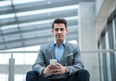 A portrait of young businessman with smartphone sitting in corridor outside office.