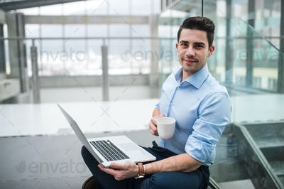 A portrait of young businessman with laptop sitting in corridor outside office.