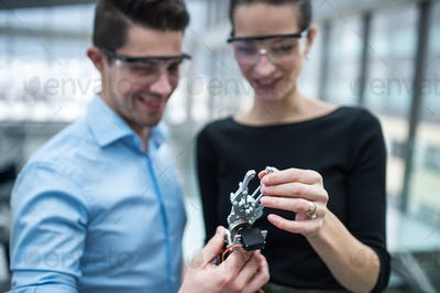 Two young businesspeople or scientists with robotic hand standing in office, talking.