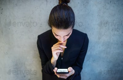 A top view of young business woman with smartphone standing against concrete wall in office.