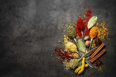 Set of various spices  on black stone background.