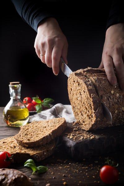 Female hands slicing homemade multigrain bread