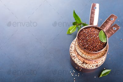 Stack of three copper measuring cups with mixed raw quinoa