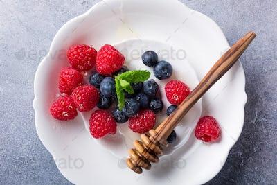 Freshly picked blueberries and raspberries on white plate