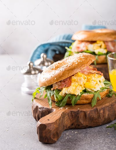 Bagels with scrambled eggs, rucola and fried bacon