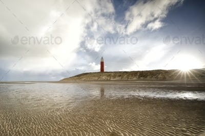 sunshine behind red lighthouse by North sea coast