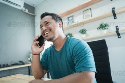portrait of smile businessman listen a good news with smartphone