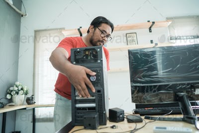 portrait of asian young man fix a problem with server of personal computer