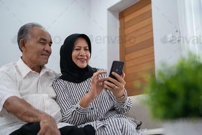 mature asian couple using smartphone