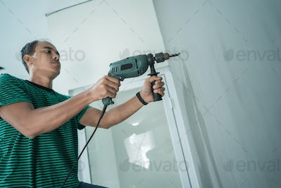 portrait of young worker use a drill make hole for a hangers on the wall