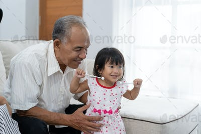 togetherness a grandfather with her little princess when a break playing a music instrument