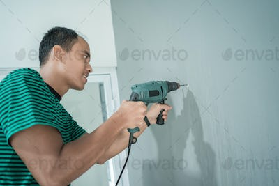 portrait of young man used a drill on the wall