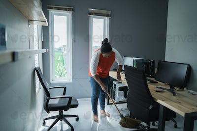 portrait of young woman cleaning floor a office room